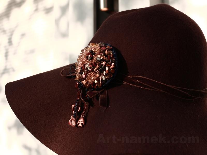 Фото бисерной броши на коричневой шляпке.