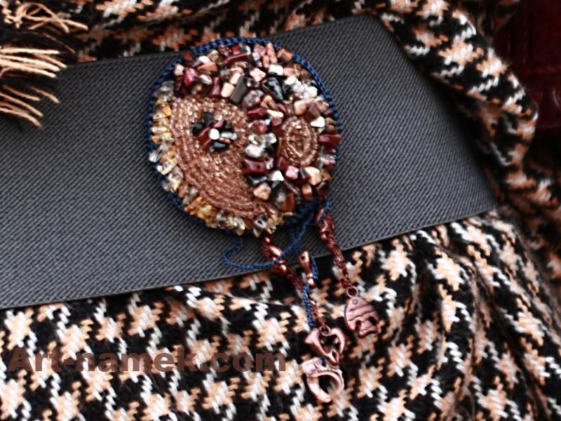 Бисерная брошь с бусинами и подвесками бежево-коричневая на сером поясе.