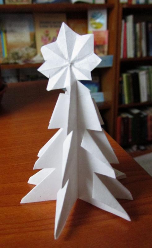 ёлочка из белой бумаги стоит на столе