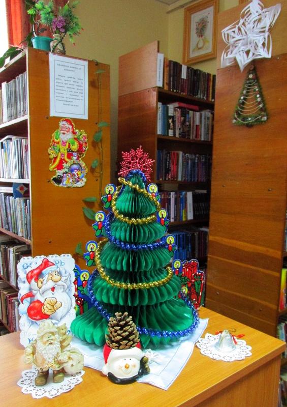 Елка из зелёной бумаги со свечечками стоит на столе.