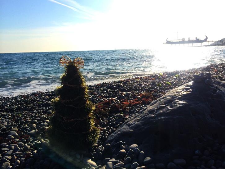 вязанная ёлочка стоит на прибрежной гальке у моря.