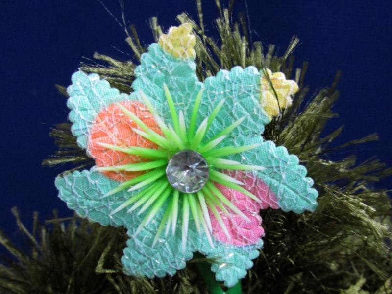 Детская заколка-цветочек на верхушке ёлочки.