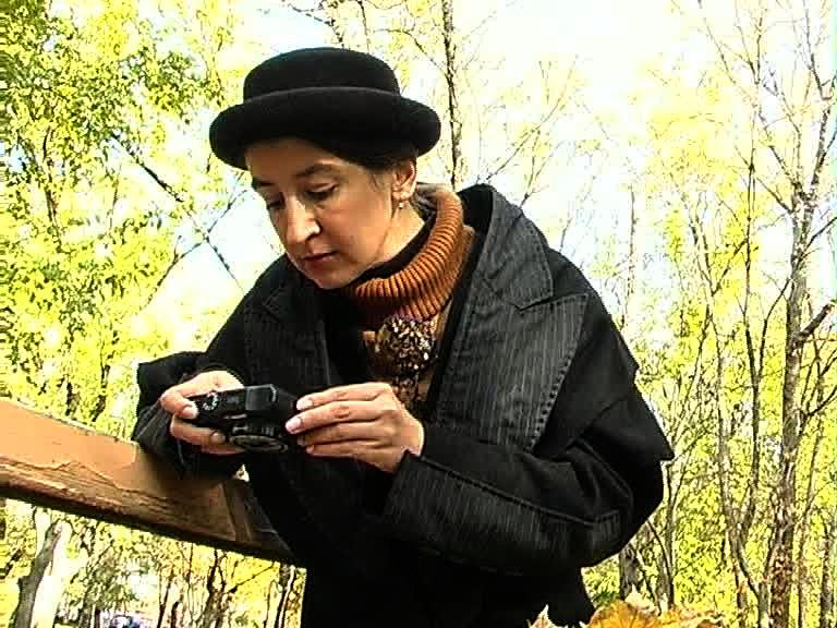 Художница фотографирует композицию из природного материала.