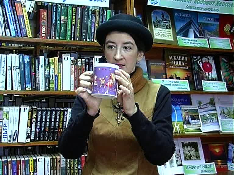 Фотохудожница показывает чашку со своим принтом.