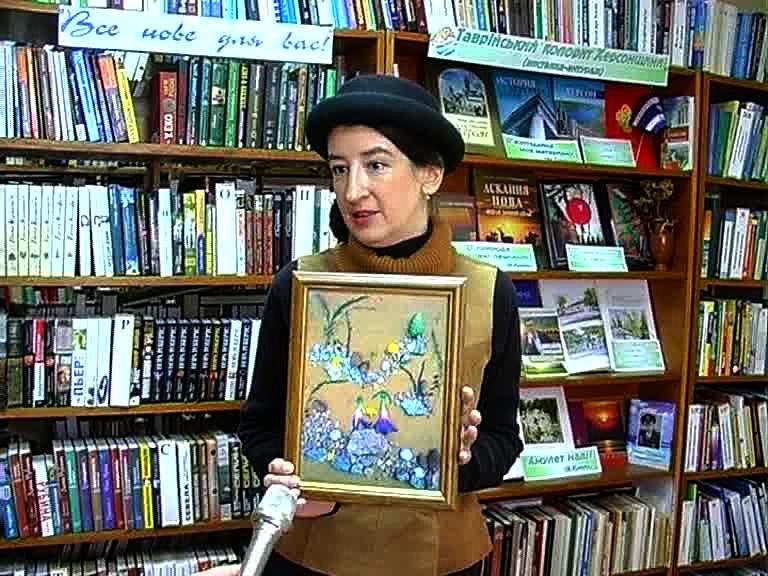 Фотохудожница показывает свою работу в деревянной рамочке.