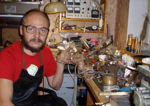 Мужчина в очках сидит возле рабочего стола