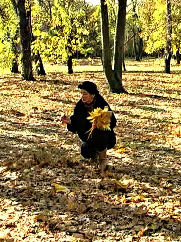 Художница собирает осенние листья.