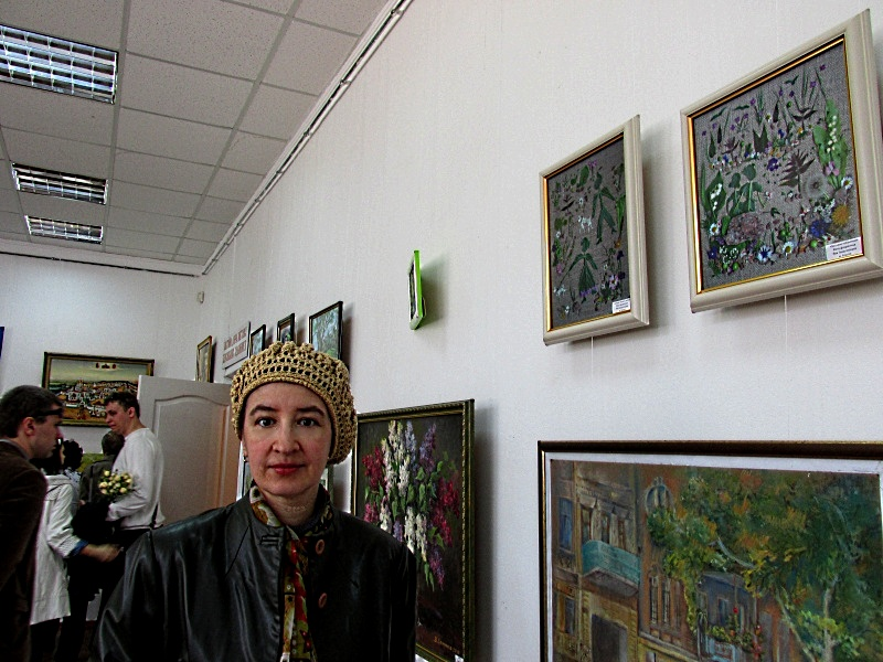 Artists at art exhibition near her woks.